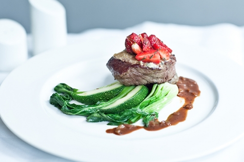 Beef Tenderloin Steak Dressed with Blue Cheese Served on Green Vegetables